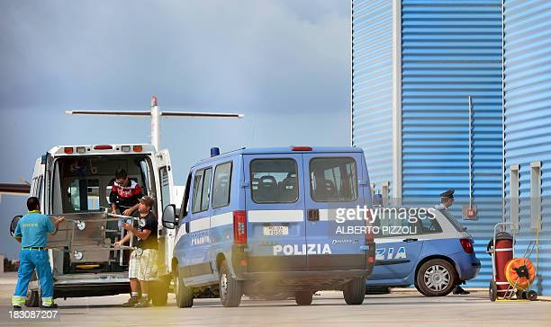 An ambulance arrives at the Lampedusa airport where bodies of migrants are transported on October 4, 2013. Italy mourned today the 300 African...