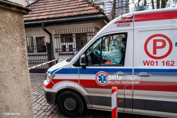 An ambulance car with a driver wearing a protective suit passes the gate of the infectious hospital in Warsaw where two patients with confirmed...