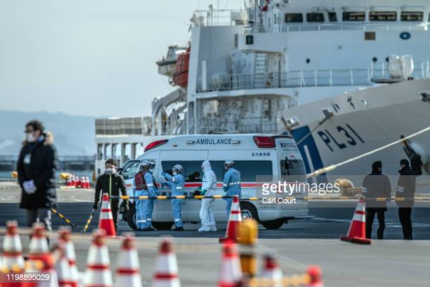 An ambulance carries a coronavirus victim from the Diamond Princess cruise ship while it is docked at Daikoku Pier where it will be resupplied and...