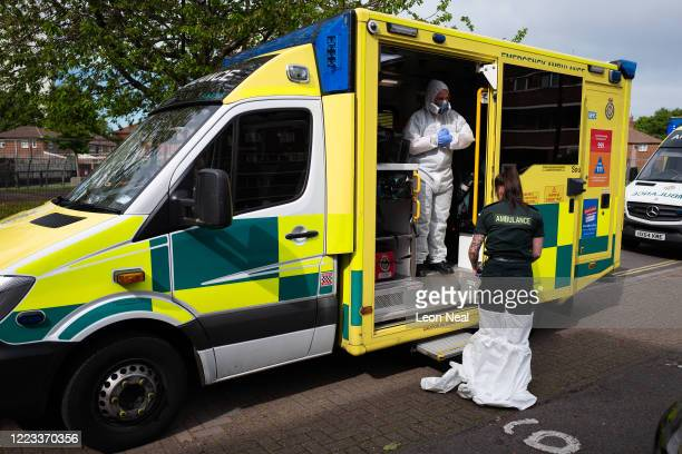 An ambulance crew from the South Central Ambulance Service remove their PPE3-level clothing after responding to a false alarm call for a heart attack...