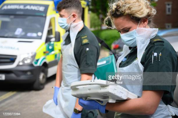 An ambulance crew from the South Central Ambulance Service wear protective clothing as they complete the digital paperwork after responding to a...