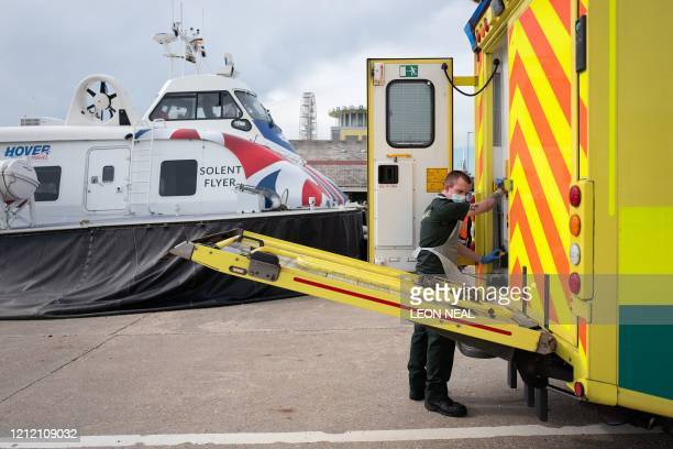 An ambulance crew member from the South Central Ambulance Service loads a patient into an ambulance after she was transported from the Isle of Wight...