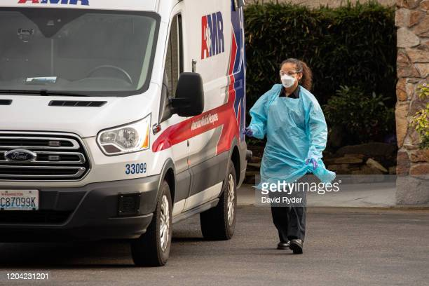 An ambulance driver prepares to leave after transporting a patient into an ambulance at Life Care Center of Kirkland on February 29 2020 in Kirkland...