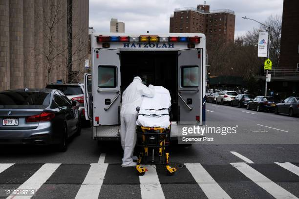 An ambulance driver puts away and cleans a medical gurney outside of Mount Sinai Hospital which has seen a surge in coronavirus patients on March 31...