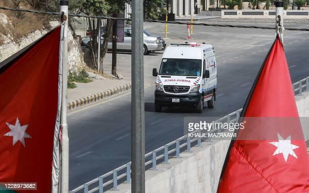An ambulance drives along an empty road during a COVID-19 coronavirus lockdown in Jordan's capital Amman on October 9, 2020.