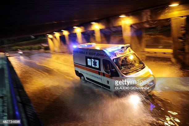 An ambulance drives down a flooded street in downtown Florence late on August 1 2015 Some twenty people were wounded on August 1 when a tornado...