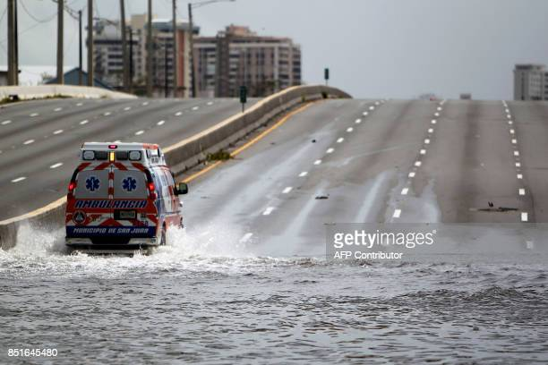 An ambulance drives on a flooded street in the aftermath of Hurricane Maria in San Juan Puerto Rico on September 22 2017 Puerto Rico battled...