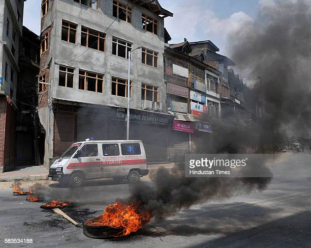 An ambulance drives past a burning tire put by protesters as a blockade after state authorities lifted 17 days curfew on July 26 2016 in Srinagar...