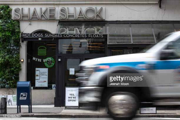 An ambulance drives past a Shake Shack restaurant on April 20, 2020 in New York City. Shake Shack announced that they will return a $10 million...