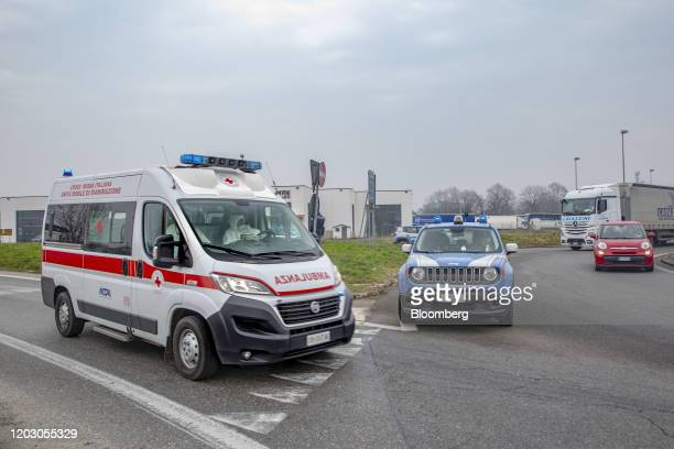 An ambulance drives past a yellow zone quarantine roadblock near the quarantine red zone in the town of Codogno in Guardamiglio Italy on Tuesday Feb...