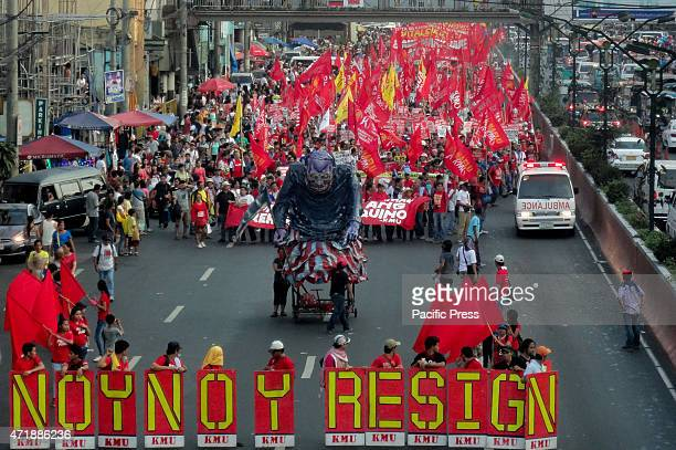 An ambulance drives past marching protesters center right as protesters march along Quiapo district alongside an effigy depicting Philippine...