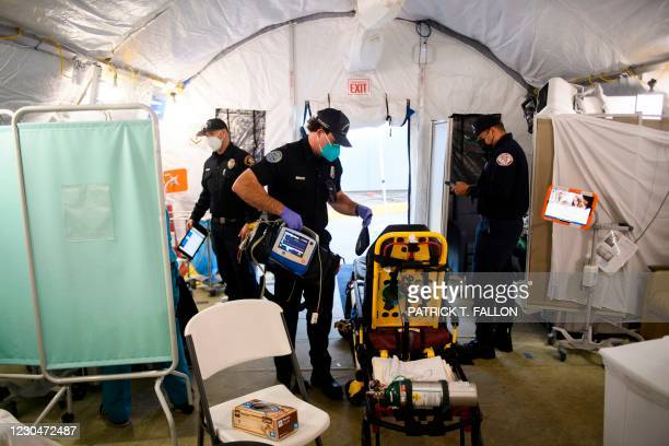 An ambulance emergency medical technician packs up equipment while wearing personal protective equipment after transferring a patient to a suspected...