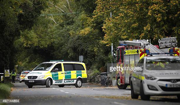 An ambulance is driven at the police cordon outside the halting site in the south Dublin suburb of Carrickmines Ireland on October 10 2015 where a...