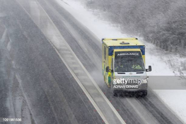 An ambulance is driven through snow and sleet as it travels along the A34 road near Chievely in Berkshire west of London on February 1 2019 Snowfall...