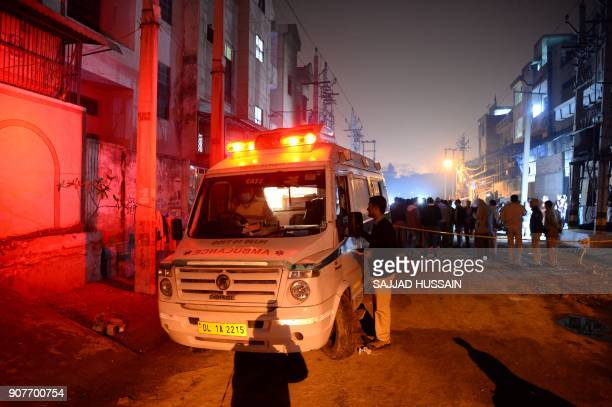 An ambulance is parked in front of a plastic factory in the Bawana industrial area on the northern edge of New Delhi on January 20 2018 after a fire...