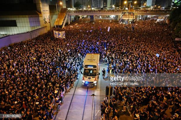 TOPSHOT An ambulance is pictured surrounded by thousands of protesters dressed in black during a new rally against a controversial extradition law...