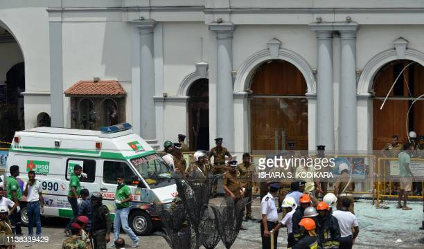TOPSHOT An ambulance is seen outside the church premises with gathered security personnel following a blast at the St Anthony's Shrine in Kochchikade...