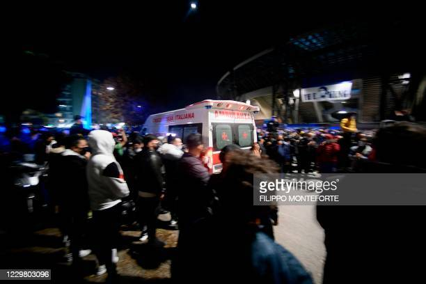 An ambulance of the Italian Red Cross drives past as fans and people gather outside the San Paolo stadium in Naples on November 26, 2020 to mourn the...
