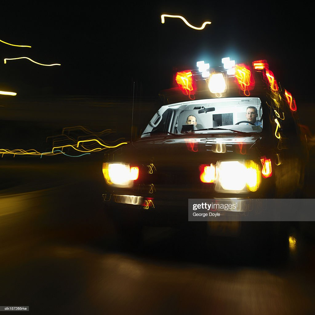An ambulance on the road at night with two young paramedics inside (blurred) : Stock Photo