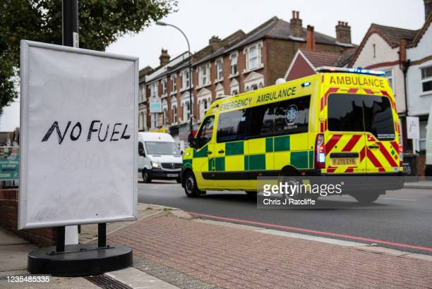 An Ambulance passes a sign outside an Esso garage informing the public that they have no fuel on September 25, 2021 in Catford, London, United...