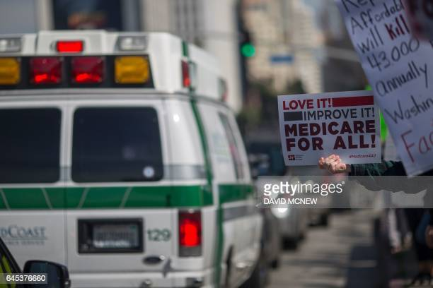 An ambulance passes people protesting Trump administration policies that threaten the Affordable Care Act Medicare and Medicaid near the Wilshire...