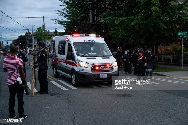 An ambulance passes through police barricades as demonstrators face off with law enforcement personnel near the Seattle Police Departments East...