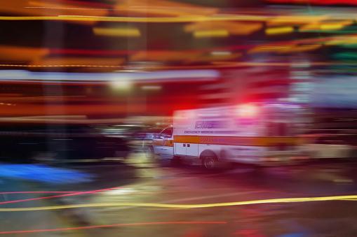 An ambulance speeding through traffic at nighttime 1083429024
