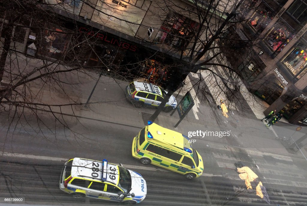 TOPSHOT - An ambulance standsa near covered bodies at the scene where a truck crashed into the Ahlens department store at Drottninggatan in central Stockholm, April 7, 2017. News Agency / Privat / Sweden OUT