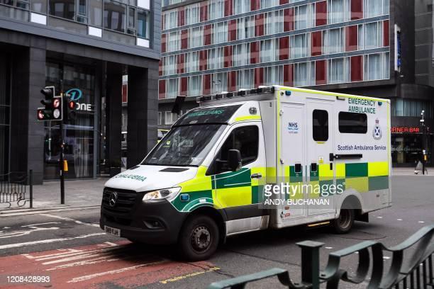 An ambulance travels through Glasgow city centre on March 27, 2020. - Britain is under lockdown, its population joining around 1.7 billion people...