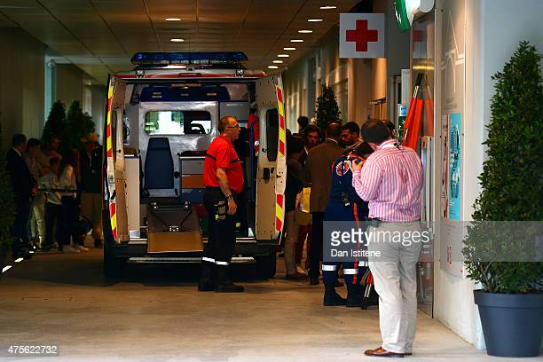 An ambulance waits to transport an injured spectator to hospital after a piece of the scoreboard above Court Philippe Chatrier was blown off in high...