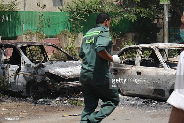 An ambulance worker rushes by charred cars-turned-barricades in Rabaa, the site of one of the two sit-ins Egyptian forces sought to break up,...
