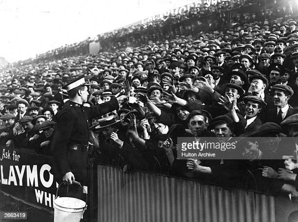 An ambulanceman in attendance at the match between Tottenham Hotspur and Manchester City hands out water to supporters sweltering in the heat