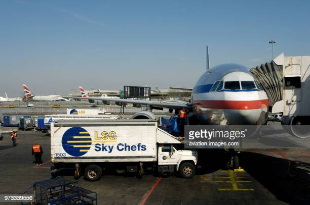 an American Airlines Airbus A300600R parked at the terminal with LSG Sky Chefs catering trucks and jetway attached