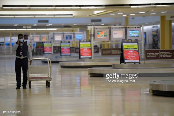 An American Airlines baggage service personnel walks among a deserted baggage clam area at Reagan National Airport in Arlington VA on April 30 2020
