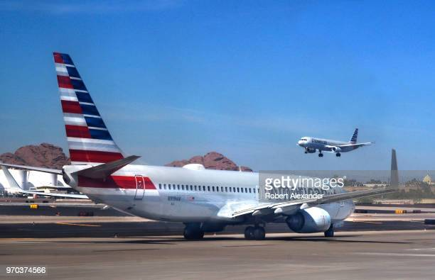 An American Airlines commercial jet takes off as another taxis to its gate at Phoenix Sky Harbor International Airport in Phoenix Arizona