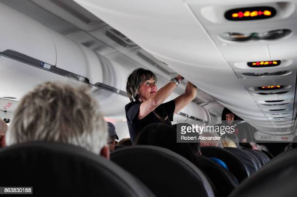An American Airlines flight attendant closes the lid on an overhead luggage compartment in a passenger jet preparing to depart from Dallas/Fort Worth...