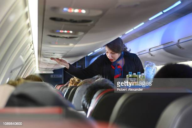 An American Airlines flight attendant serves drinks to passengers after departing Dallas/Fort Worth International Airport.