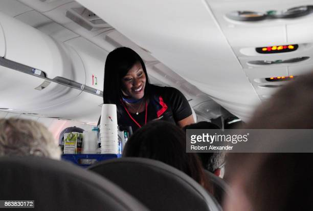 An American Airlines flight attendant serves drinks to passengers after departing from Dallas/Fort Worth International Airport in Texas