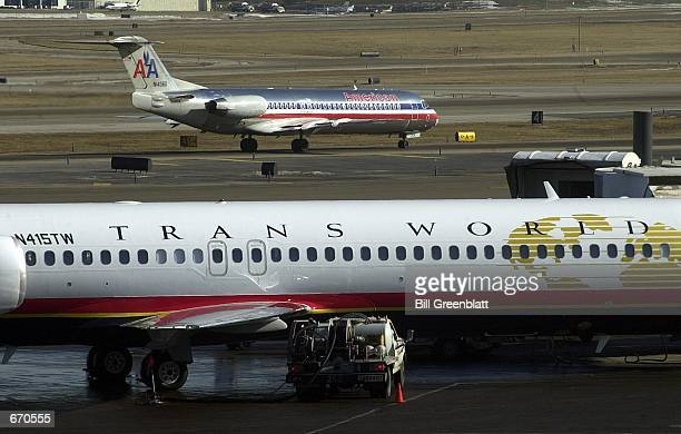 An American Airlines flight passes by a Trans world Airlines plane at the gate as it taxi's out January 9 2001 from LambertSt Louis International...