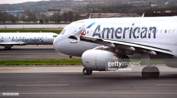 An American Airlines ground handling crew member pushes an Embraer 175 plane from a gate to the runway at Ronald Reagan Washington National Airport...