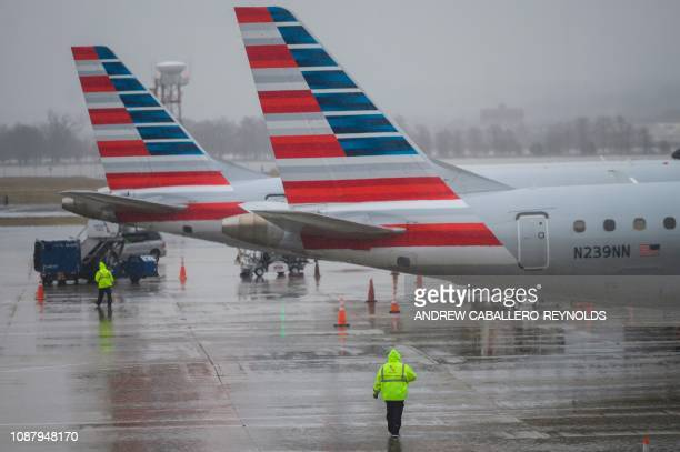 An American Airlines ground staff member walks towards planes on the tarmac at Ronald Reagan Washington National Airport in Arlington, Virginia on...