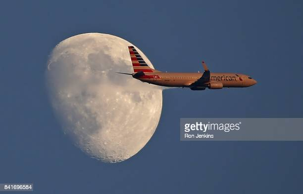 An American Airlines jetliner flies past the moon as the Los Angeles Angels of Anaheim play the Texas Rangers during the first inning at Globe Life...