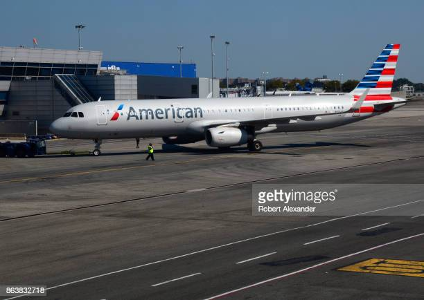 An American Airlines passenger jet is towed to a gate at John F Kennedy International Airport in New York New York