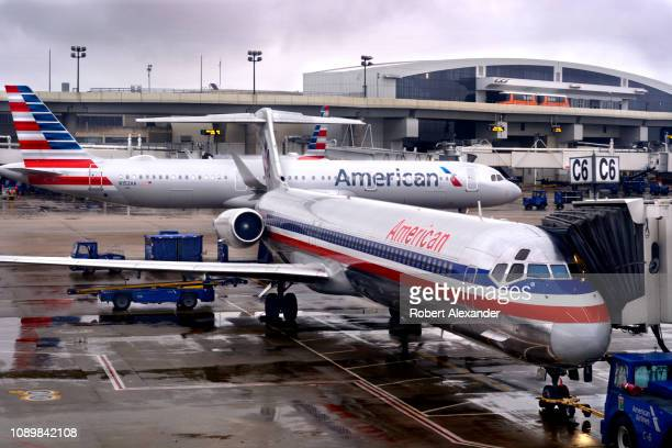 An American Airlines passenger jet taxis past another American Airlines plane parked at a gate on a rainy morning at Dallas/Fort Worth International...