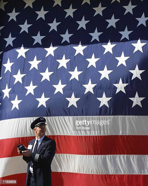An American Airlines pilot looks up towards the sky as a jet passes overhead while standing in front of a large American flag after President George...