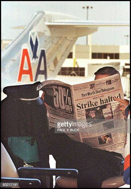 An American Airlines pilot reads a newspaper before boarding his aircraft at DallasFt Worth Airport 15 February US President Bill Clinton imposed a...