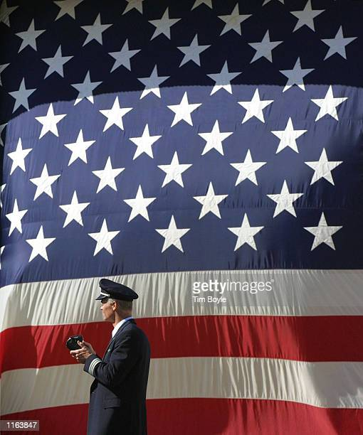 An American Airlines pilot walks in front of a large American flag after President George W Bush spoke at a rally September 27 2001 at O''Hare...