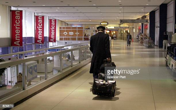 An American Airlines pilot walks through John F Kennedy International airport March 2 2001 in New York City A federal judge issued a temporary...