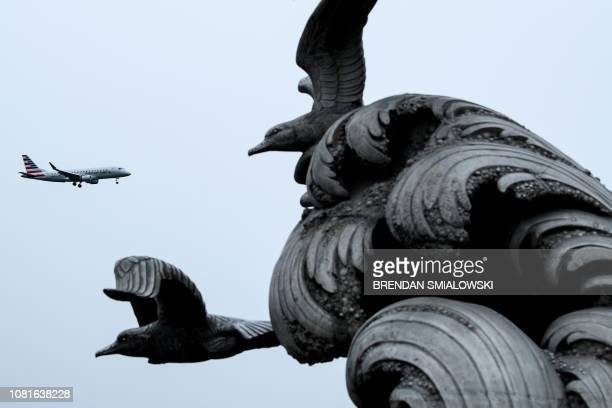 An American Airlines plain passes the Navy Merchant Marine Memorial as it lands at Ronald Reagan Washington National Airport during the 22nd day of...
