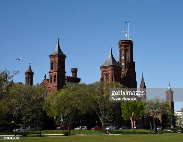 An American Airlines plane departing nearby Ronald Reagan Washington National Airport flies near the Smithsonian Institution Building, popularly...